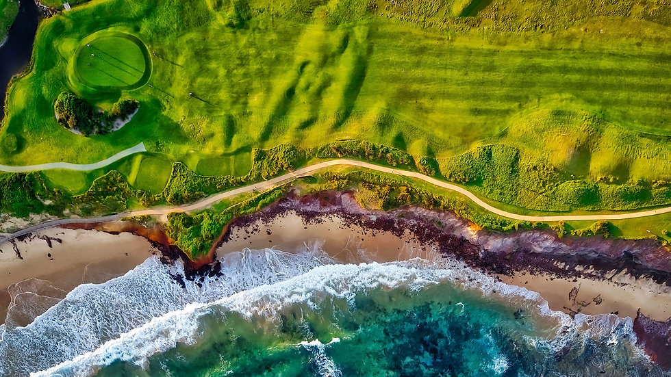 Aerial view of walking path on cliff top along coastline