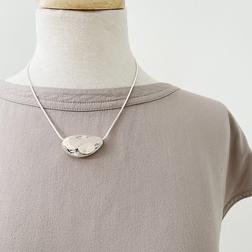 Necklace with textured silver metallic piece