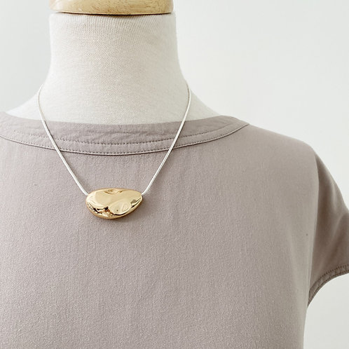 Necklace with textured gold metallic piece
