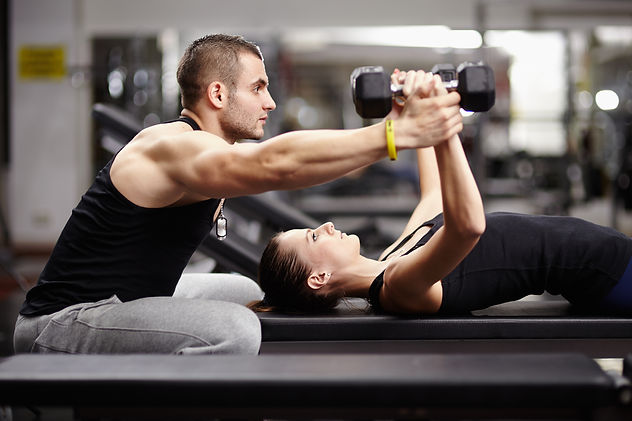 Personal trainer helping woman working w