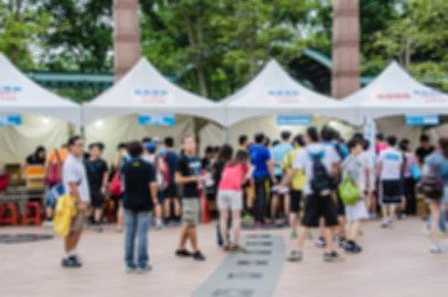 Blurred image of sport and festival events with people before white tents. .jpg