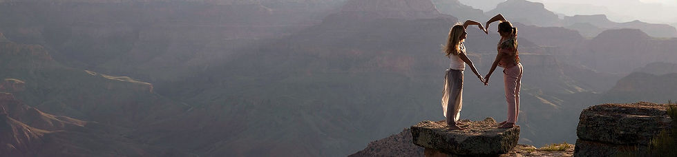 two girls building a heart on the spectacular background of the grand canyon