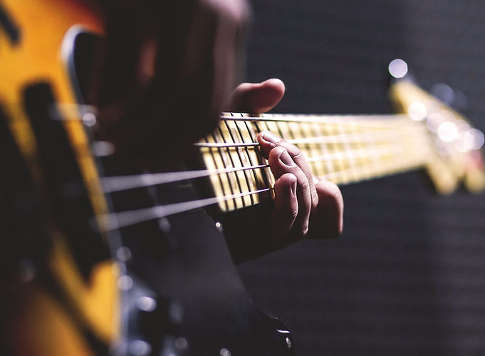 person-playing-sun-burst-electric-bass-g