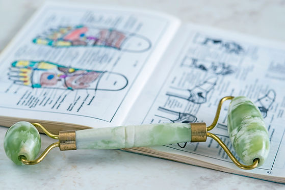 jade roller placed on top of a reflexology book