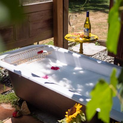 warm oudoor bubbly bath under grape leav