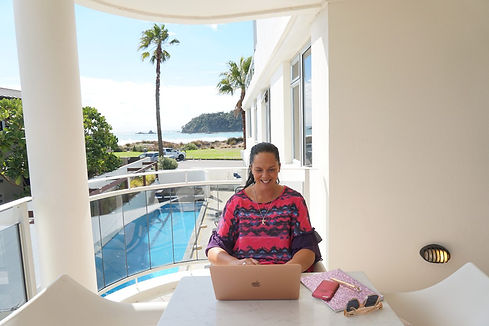 Young woman working on Mac laptop on apartment balcony