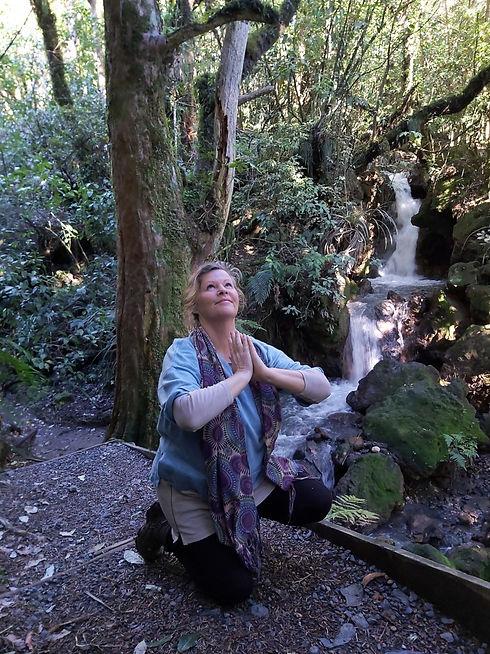 Woman praying by a waterfall