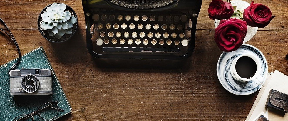 Vintage typewriter on wooden desk with camera and red roses