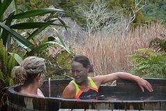 Women in togs in a hot tub outside