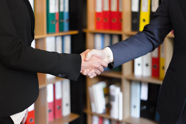Two women in business suits shaking hands