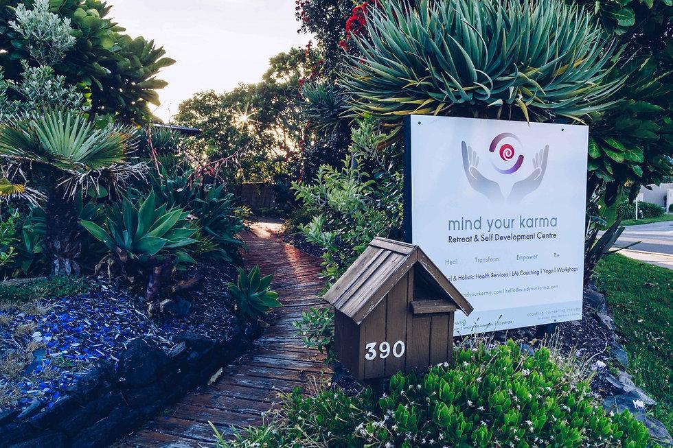 Mind Your Karma sign in beautiful native garden