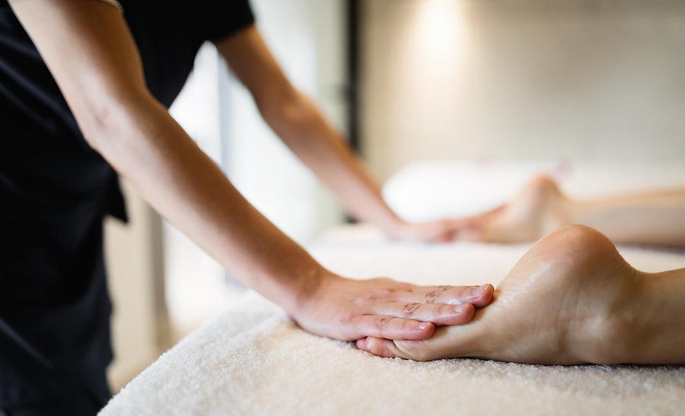 Masseuse massaging feet of person at mas