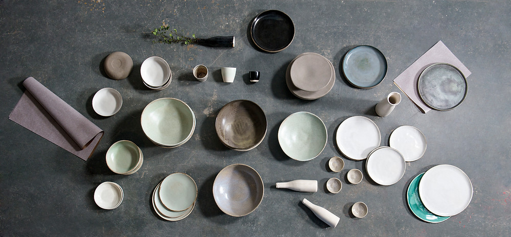 neat flatlay arrangement of modern handcrafted ceramic dishes and bowls