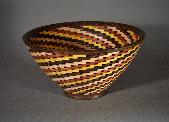 This is a open segmented wood bowl with a tornado pattern.