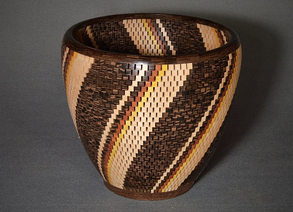 This open segmented wood vessel has a twist design.