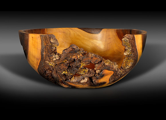 This hand turned wooden bowl is made out of walnut with the natural edge and bark left on it.