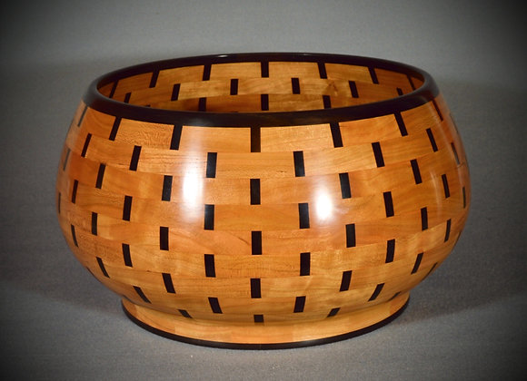 This segmented wood bowl is made out of cherry with ebony to give the look of a basket.