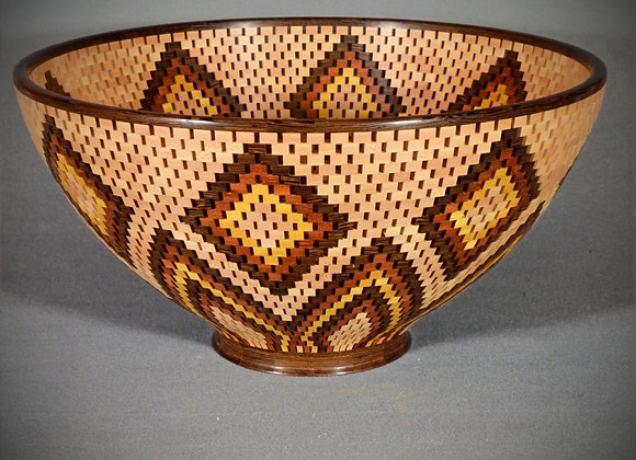 This large open segmented wood bowl has a beautiful design made from different species of wood.