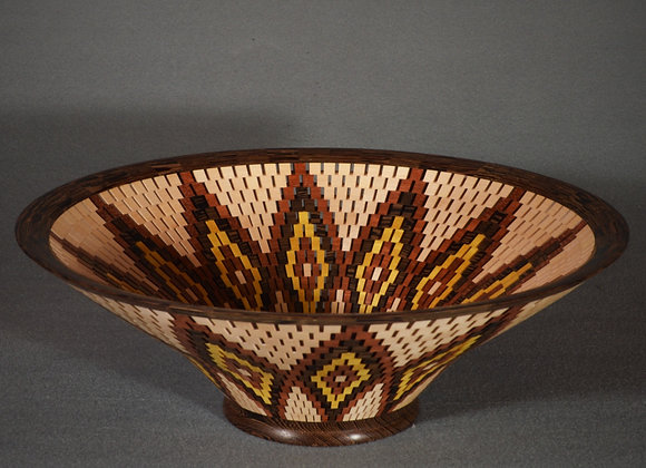 This open segmented wood bowl has a flower petal design made out of different species of wood.