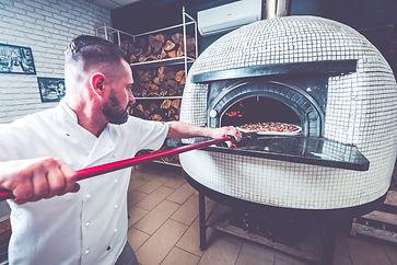 bearded-man-chef-preparing-pizza-at-loca