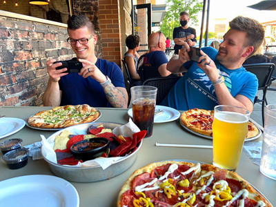 two men taking photos of their food using smartphones chips and beer visible