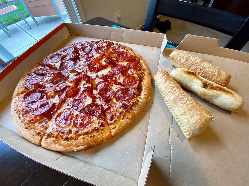 pepperoni pizza on table next to stuffed breadsticks