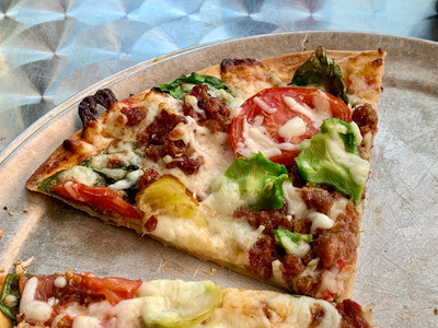slice of pizza with avocado and bacon