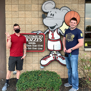 posing by the mozzi pizza sign