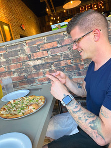man with glasses and apple watch taking photo of food at restaurant
