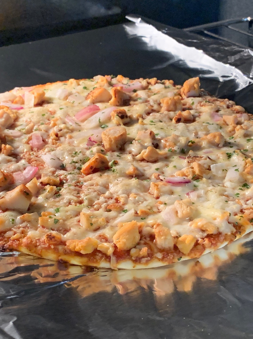 pizza cooking in oven with chicken and bbq sauce