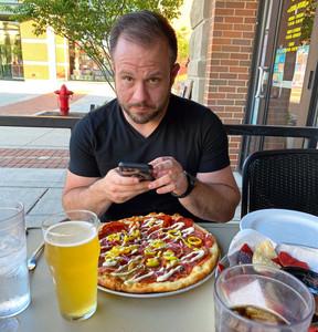 man looks at camera while taking photo of food at restaurant