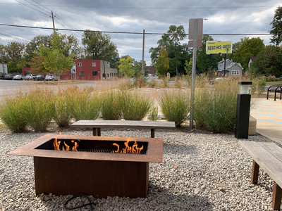 gas fire pit next to tall grass in parking lot
