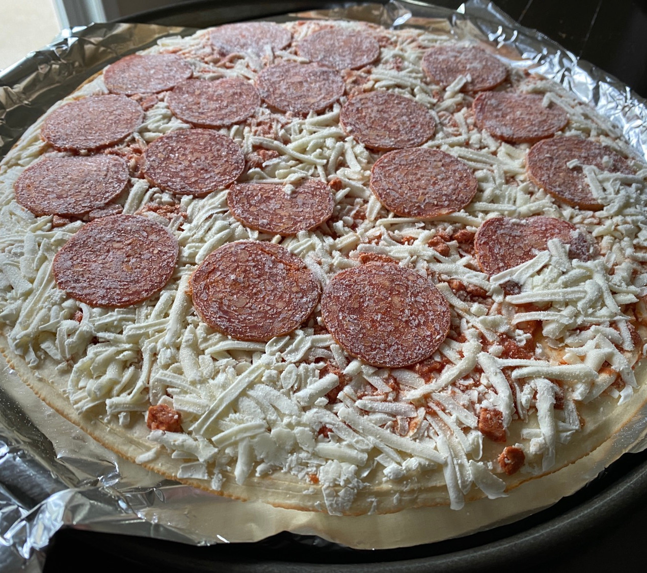 natural light photo of frozen pepperoni pizza still frozen