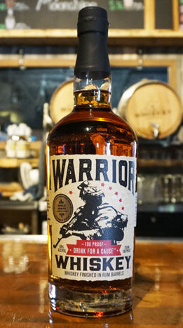 Steamboat Whiskey Company's award-winning Warrior Whiskey shown on a wooden bar top