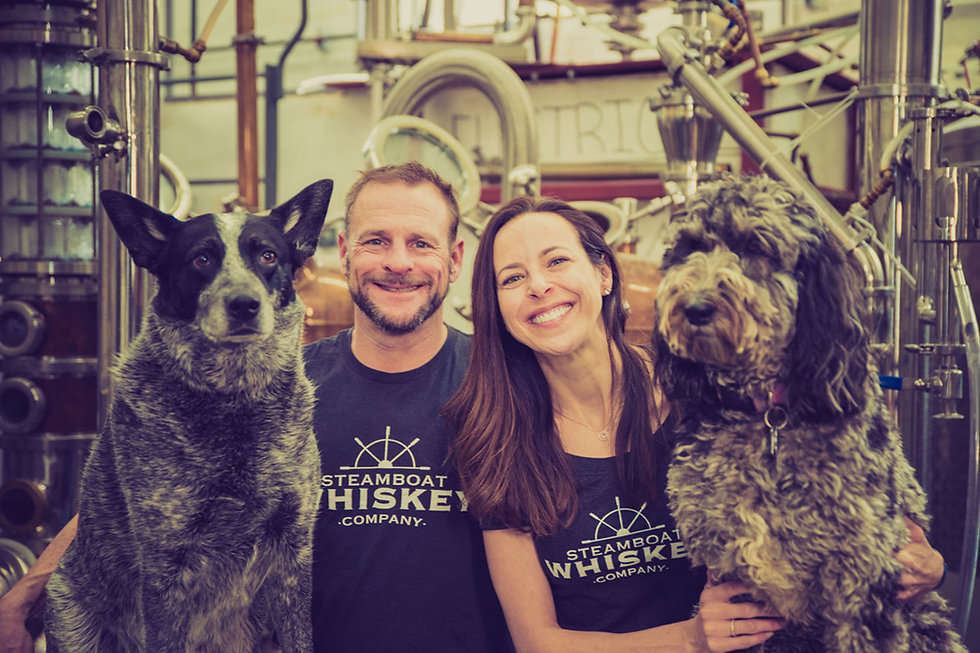 Nathan and Jessica Newhall, founders of Steamboat Whiskey Company, pose in the distillery with their dogs, Romeo and Roxy.