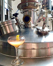 A cocktail in a glass is shown in front of distilling equipment