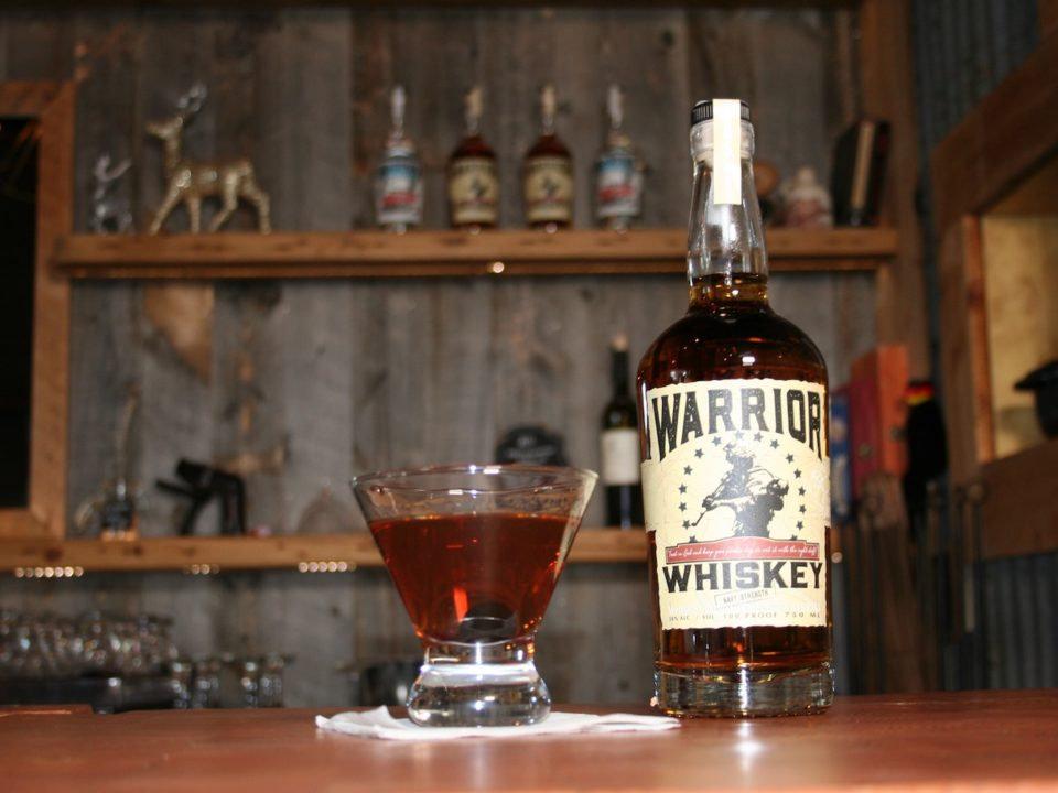 "A ""Mountain Smoke"" cocktail shown next to a bottle of Warrior Whiskey"