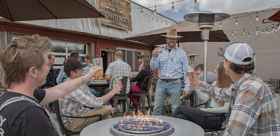 Patrons sit at a fire table on the patio at Steamboat Whiskey Company and toast toward a man wearing a blue shirt and a tan hat.