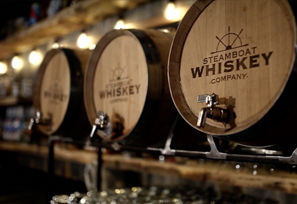 Tapped whiskey barrels displaying the distillery's logo sit behind the bar at Steamboat Whiskey Company
