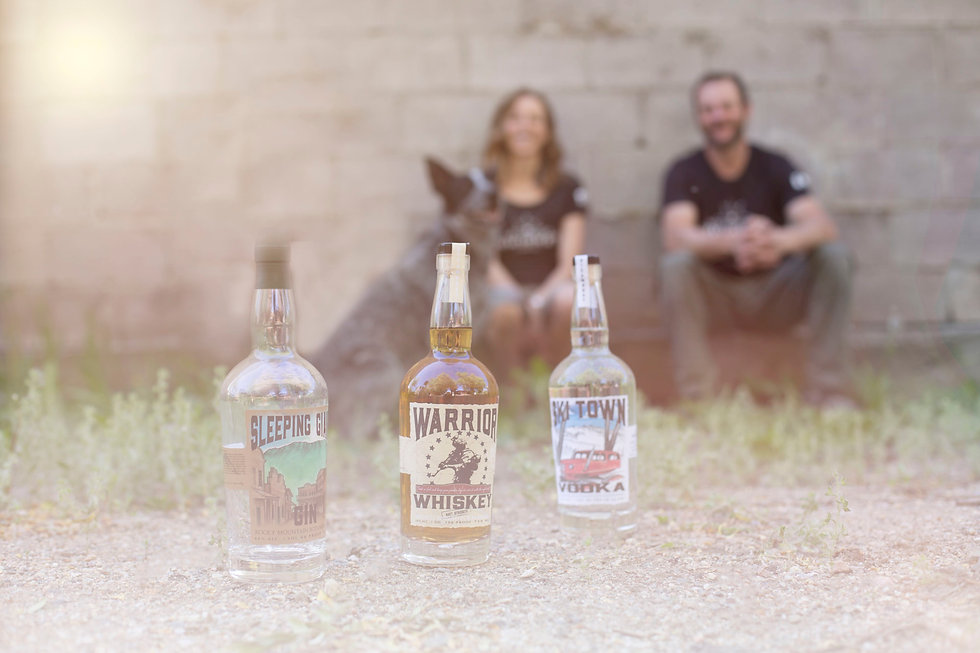 Bottles of Steamboat Whiskey Company spirits in the foreground with business owners in the background