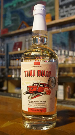 Steamboat Whiskey Company's award-winning Tiki Rum shown on a wooden bar top