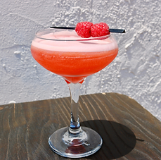 A vibrant drink in a glass with raspberry garnish shown on a picnic table