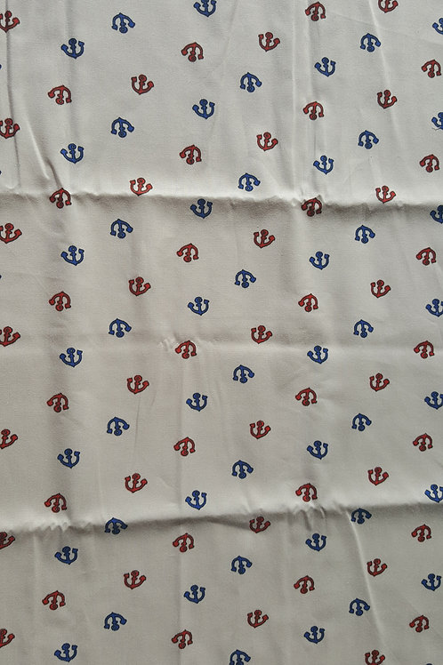 Tela 100% algodón de 40 x 50 cm en color beige con anclas rojas y azules.