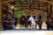 Sterling riders and horses pose in an archway at a horse show