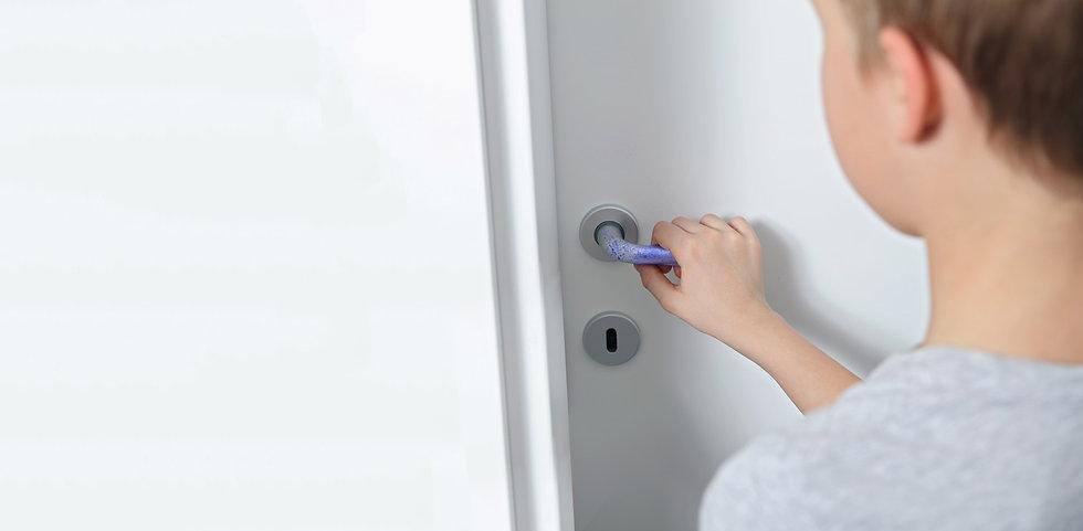 Little boy grabbing door handle with coronavirus on it