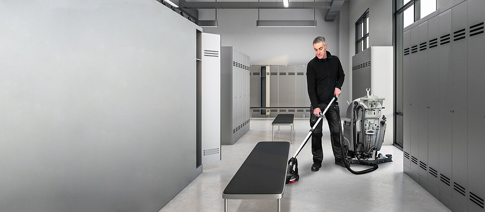 Male using MotorScrubber FORCE to clean underneath seating in a changing room.