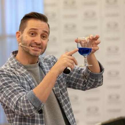 Teacher Holding A Glass Of Blue Dye