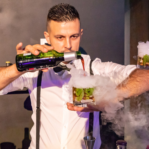 Bartender Pouring Cocktail Into A Glass Thats Smoking And Balancing On His Arm
