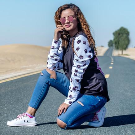Female Model Bending Down To Pose In Al Qudra Desert