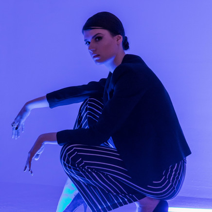 Female Model Squatting with UV Light On In The Background